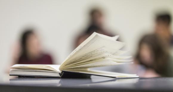 livre ouvert avec des étudiants en arrière plan.